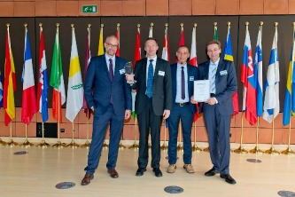 Michael Herz (v.l.n.r.), Dr. Mark Winter, Olaf Delker und Prof. Dr. Andreas Büchner bei der Preisverleihung im Delors-Gebäude der EU